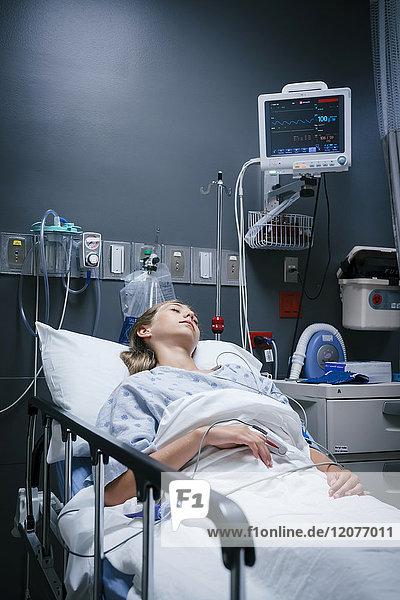 Caucasian girl sleeping in hospital bed