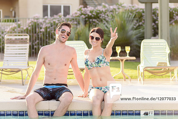 Portrait of Caucasian couple sitting at edge of swimming pool