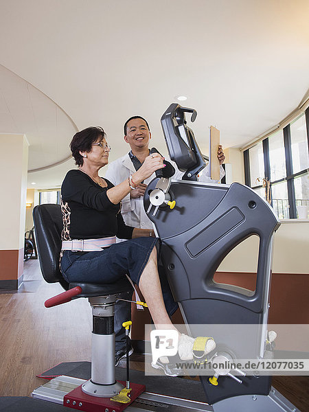 Physical therapist watching patient on exercise machine