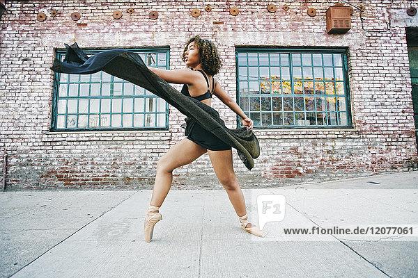 Mixed race woman dancing ballet on sidewalk