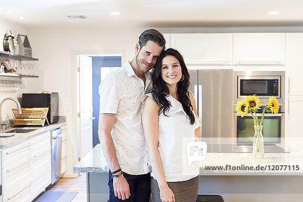 Portrait of smiling Caucasian couple standing in kitchen