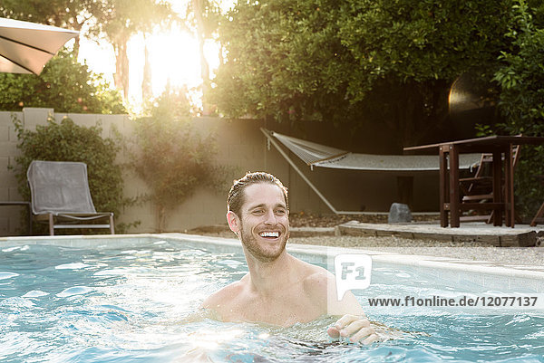 Smiling Caucasian man relaxing in swimming pool