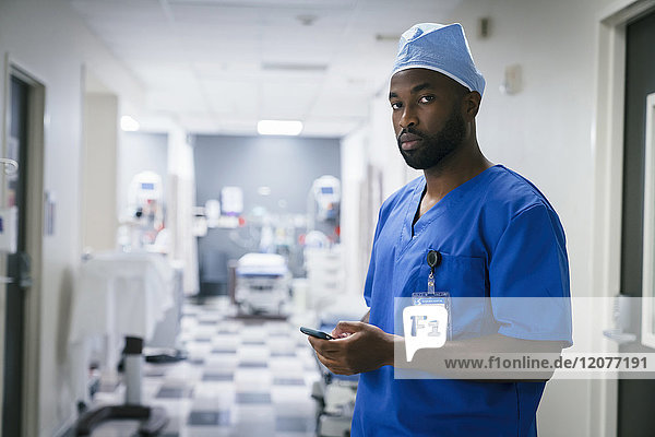 Portrait of black nurse texting on cell phone