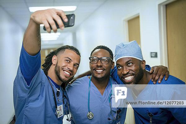 Smiling nurses posing for cell phone selfie