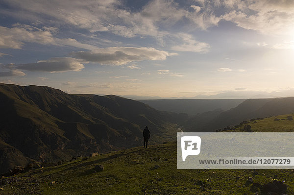 Distant Caucasian man admiring scenic view of valley