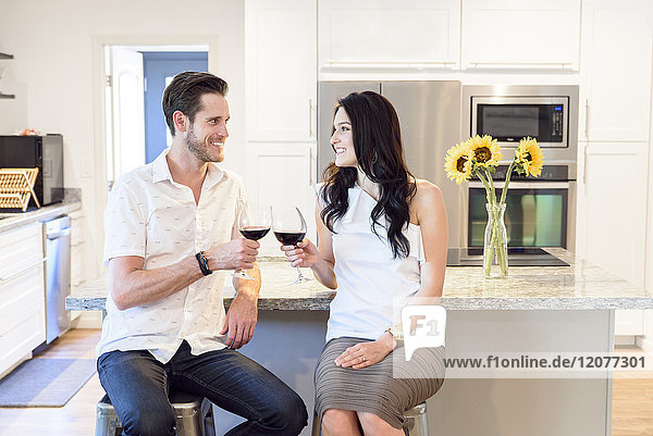 Smiling Caucasian couple toasting with red wine