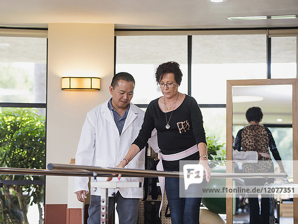 Physical therapist helping walking patient