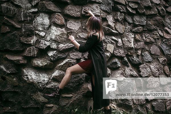 Caucasian woman climbing rock wall