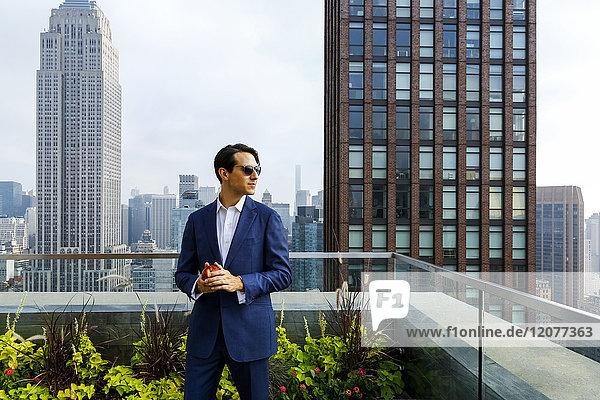 Caucasian businessman holding apple on urban rooftop