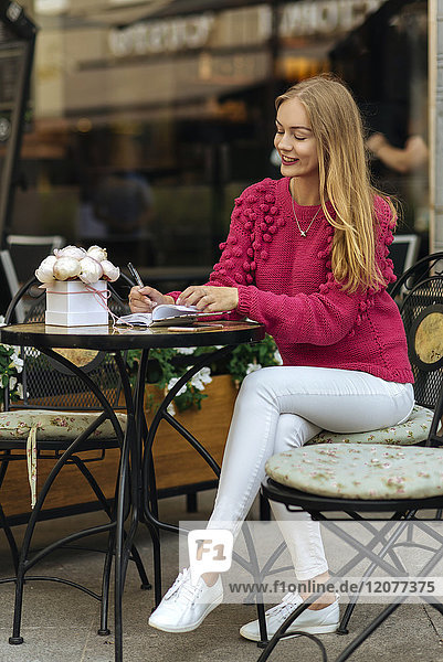 Caucasian woman sitting at table writing in journal