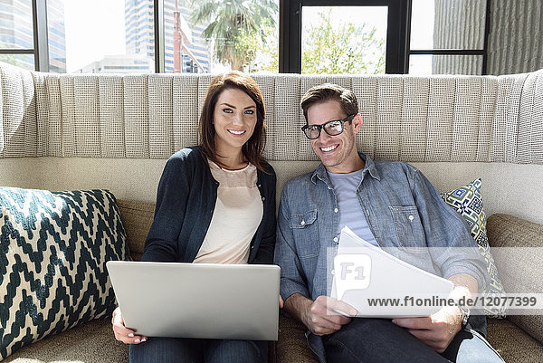 Caucasian couple on sofa holding laptop and paperwork