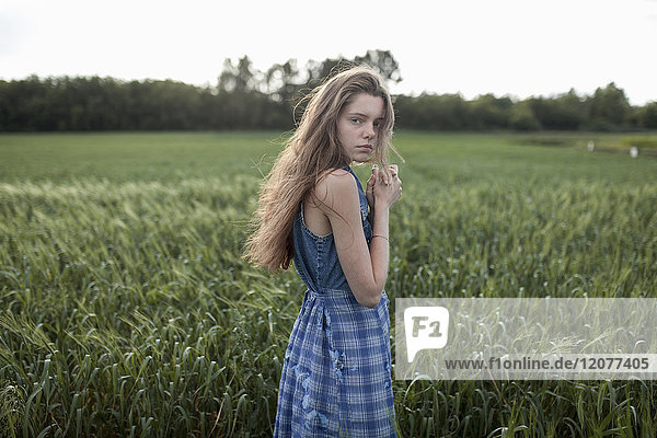 Wind blowing hair of serious Caucasian woman in field