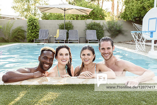 Portrait of smiling friends in swimming pool