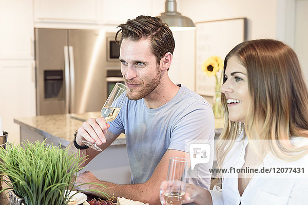Smiling Caucasian couple drinking champagne