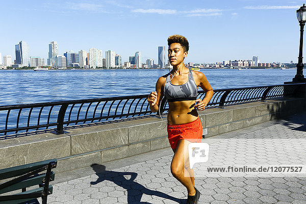 Mixed race woman running at waterfront listening to earbuds