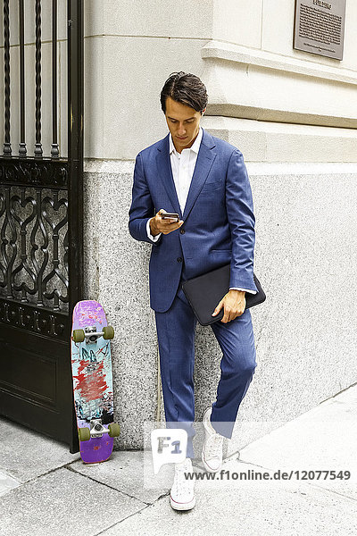 Caucasian businessman with skateboard texting on cell phone