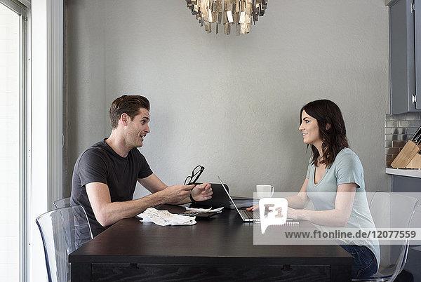 Caucasian man talking to woman with laptop