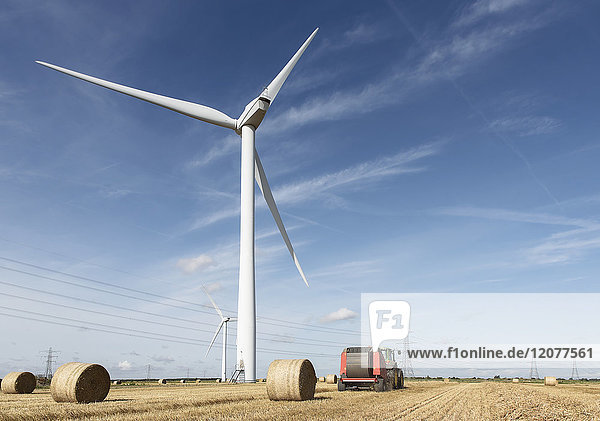 Bales of hay and tractor near wind turbine