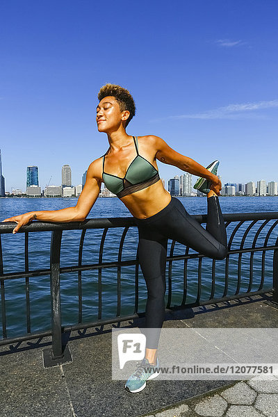 Mixed race woman stretching legs at waterfront