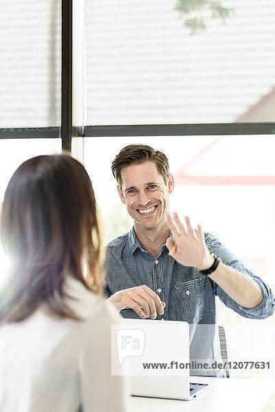 Caucasian man using laptop gesturing to woman