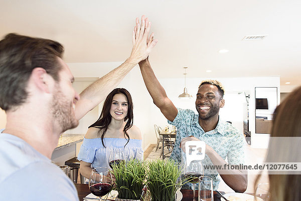Friends drinking red wine and high-fiving
