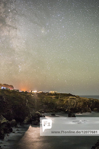 Night sky over cliff at ocean