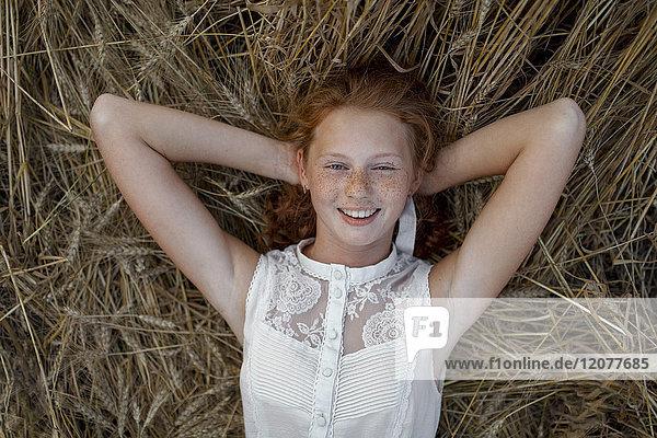 Caucasian girl laying in wheat