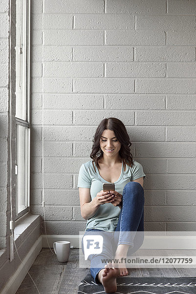 Caucasian woman sitting on floor texting on cell phone