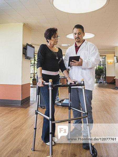 Caucasian physical therapist showing digital tablet to patient