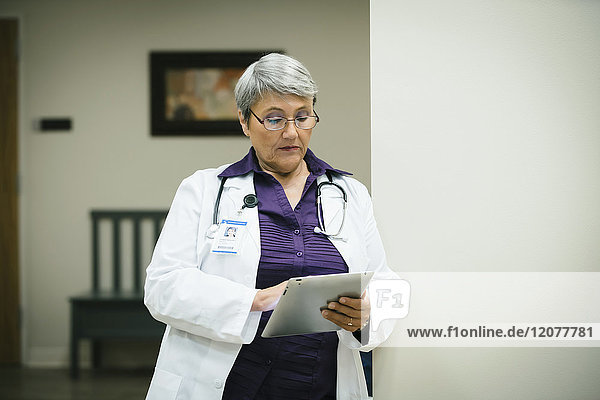 Mixed race doctor using digital tablet