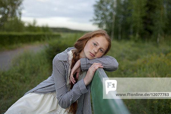 Portrait of pensive Caucasian girl sitting on bench