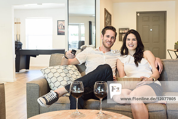 Smiling Caucasian couple sitting on sofa watching television