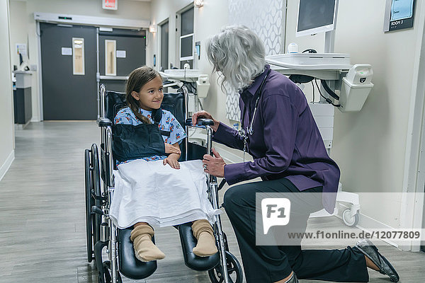 Doctor talking to girl in a wheelchair