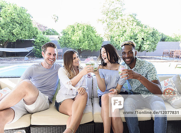 Smiling friends with cold drinks toasting outdoors