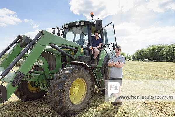 Smiling Caucasian couple posing near tractor