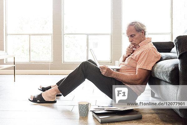 Pensive Caucasian man sitting on floor using laptop