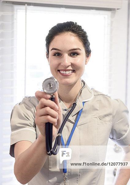 Portrait of smiling Caucasian nurse holding stethoscope