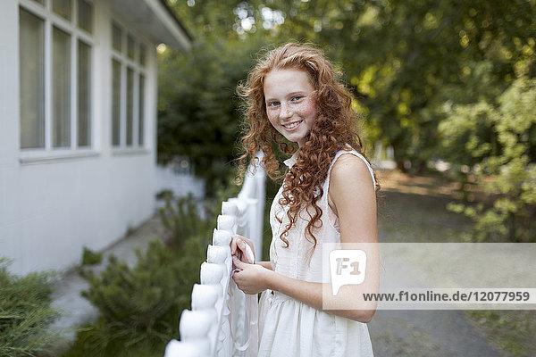 Smiling Caucasian girl standing near fence
