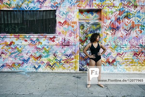 Mixed race ballet dancer resting on sidewalk Mixed race ballet dancer resting on sidewalk
