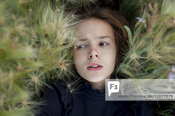 Concerned Caucasian girl laying in field