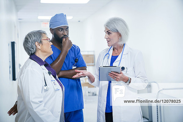 Doctors and nurse discussing digital tablet