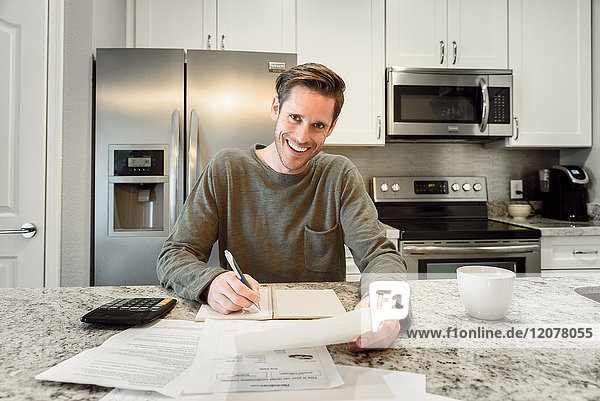 Smiling Caucasian man writing notes and reading paperwork