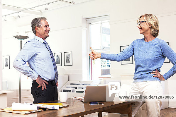 Caucasian businesswoman gesturing thumbs-up to businessman, Caucasian businesswoman gesturing thumbs-up to businessman