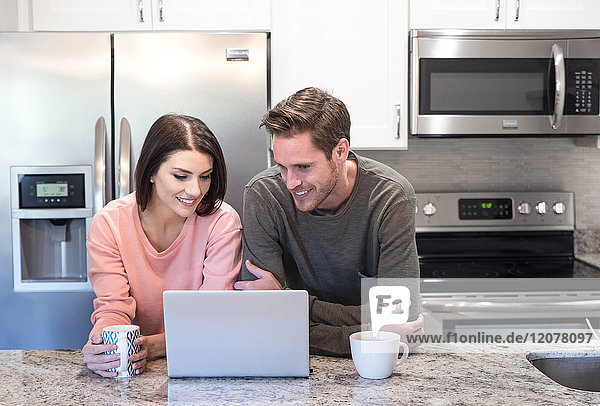 Caucasian couple drinking coffee and using laptop in kitchen