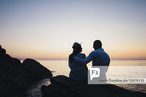 Silhouette of Caucasian couple sitting on rock near ocean at sunset