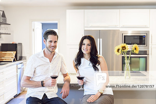 Smiling Caucasian couple drinking red wine in kitchen