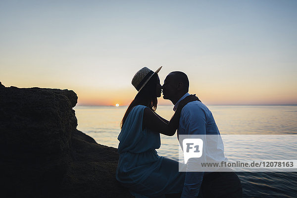 Caucasian couple kissing on rock near ocean at sunset