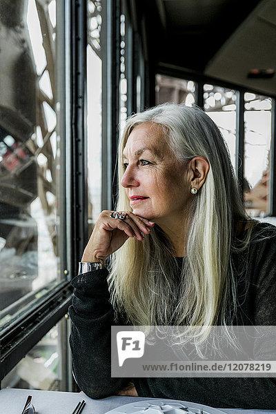 Caucasian woman admiring scenic view from restaurant window