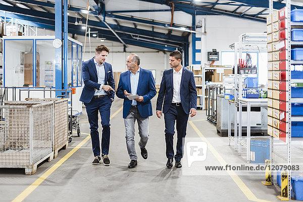 Drei Geschäftsleute gehen durch die Werkstatt und diskutieren Entscheidungen.