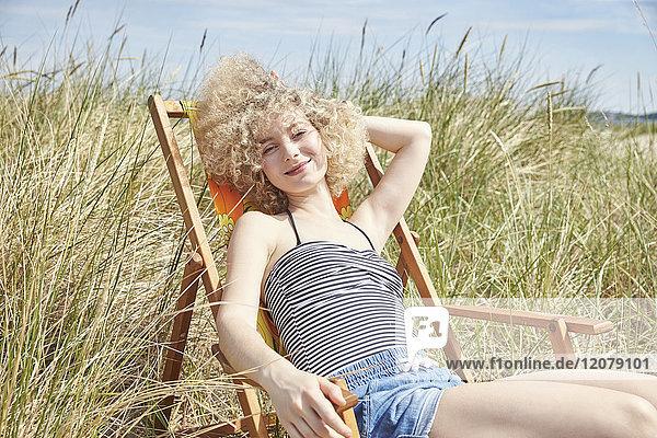 Porträt einer glücklichen jungen Frau  die auf einem Strandkorb in den Dünen sitzt.